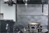Obr. 2: Pracovní prostor stroje WeldPrint 5AX s výměníkem nástrojů, pracovním vřetenem a navařovací hlavou