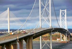 Porovnání odlišné konstrukce visutého silničního mostu (vpředu) s novým dálničním zavěšeným Queensferry Crossing v pozadí