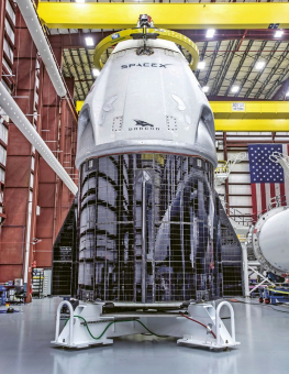 Crew Dragon během prověrek před letem DM-1 v prosinci 2018. Jde o první snímek, na kterém byly takto dobře vidět fotovoltaické panely pokrývající polovinu povrchu spodní části lodě (z druhé strany tedy nejsou). Během startu je chrání kryt, který by měl být odhozen, když se loď dostane nad husté vrstvy atmosféry. Řešení vypadá opravdu zajímavě, ale integrace panelu do povrchu nebyla údajně jednoduchá, především kvůli jejich tepelné roztažnosti