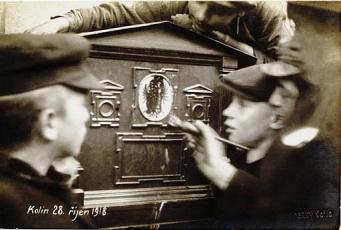 Lidé zamalovávají rakousko-uherský znak na poštovní schránce během českého převratu 28. října 1918