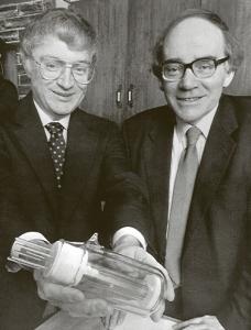 """Martin Fleischmann (vpravo) a Stanley Pons předvádějí svůj """"fúzní reaktor"""" v březnu 1989. V době, kdy jejich výsledek ještě mohl vzbuzovat optimistická očekávání, že v podobném kapesním zařízení lze snadno vyrábět prakticky neomezené množství energie."""