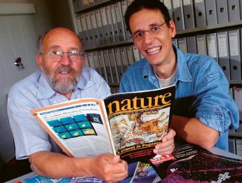 Na snímku ze srpna 2005 jsou dva nositelé Nobelovy ceny za fyziku pro rok 2019. Vlevo je Michel Mayor, vpravo Didier Queloz. V ruce drží vydání časopisu Nature, ve kterém byl zveřejněn jejich článek o objevu planety v soustavě 51 Pegasi, za který cenu získali