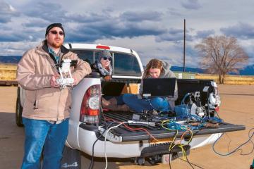 Camron Kouhestani (vlevo) pilotuje dronový systém MARCUS, zatímco Jaclynn Stubbsová (uprostřed) a Bryana Wooová (vpravo) sledují obraz na kameře, v areálu Sandia National Laboratories