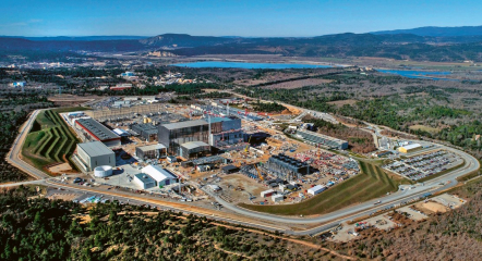 Snímek staveniště ITER na konci února 2020. Výrazná, lesklá budova uprostřed je v podstatě pouze dočasná: jde o montážní a jeřábovou halu, ve které se připravují komponenty pro samotnou budovu reaktoru. Ta na montážní halu přímo navazuje: je to její méně výrazná část vpravo. Černá budova s řadou podivných prvků na střeše jsou chladicí věže, kterými se ITER bude zbavovat přebytečného tepla. Prstenec ležící na zemi vlevo od haly je část kryostatu, světlá budova vedle něj slouží právě ke kompletaci kryostatu celého. Nad ní (s tmavou střechou a červeným pruhem) je budova pro výrobu supravodivých cívek tokamaku. Za ní pak energetická část provozu. Administrativa sídlí v kanceláře budově v pravé části snímku
