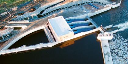 Foto z dronu zobrazuje v horní části řešení rybího schodiště vedle strojovny MVE Planá a betonový jez s propustí