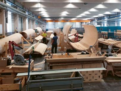 """Pohled na přípravu dílů pro modulární konstrukci 30m ověřovací větrné elektrárny společnosti Modvion. Vpravo: Její první """"dřevěná"""" elektrárna stojí nedaleko Göteborgu"""