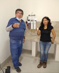 Úpravna pitné vody v areálu Laboratorio de la Minería, ambiente de Servicios Auxiliares: Dante Morales (vlevo), profesor univerzity Universidad Nacional Jorge Basadre Grohmann, vedoucí projektů čištění vod s členkou týmu Photon Energy Perú S.A.C.